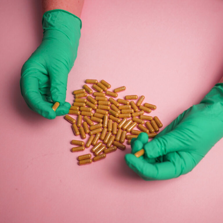 green gloves holding brown capsules on pink background